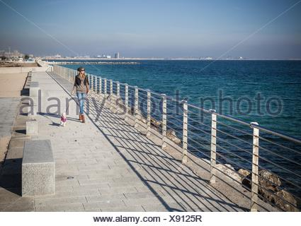 Full length front view young woman walking dog on seafront looking away