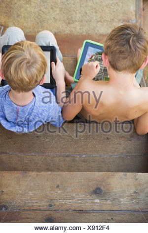 Two brothers playing on their digital tablets. - Stock Photo