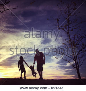 USA, California, Orange County, Father with sons at sunset - Stock Photo