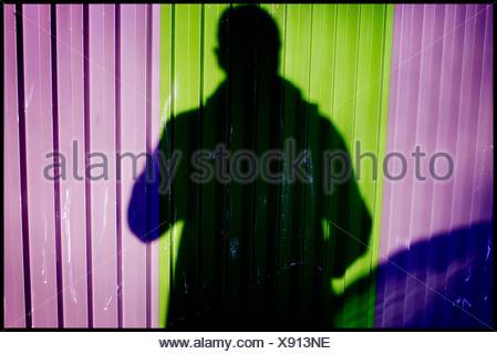 Shadow of one person cast on a colourful wall - Stock Photo