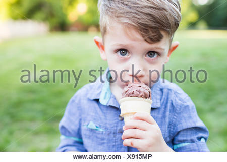 Portrait cute preschool boy eating ice cream cone - Stock Photo