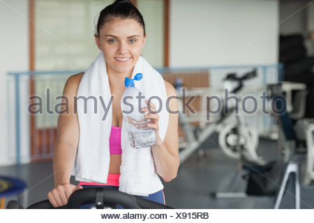 Tired woman drinking water while working out at spinning class - Stock Photo