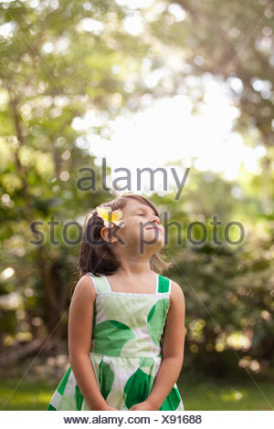 Young girl in garden, wearing flower in her hair - Stock Photo