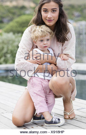 Portrait of a happy mother playing with son at poolside - Stock Photo