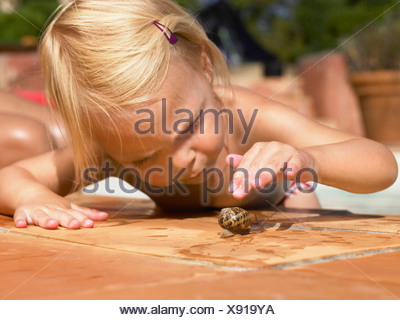 Little girl playing with a snail. - Stock Photo