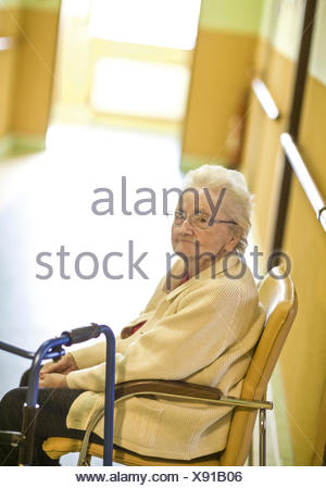 Altenheim, Seniorin sitzt am Gang auf Stuhl (model-released) - Stock Photo
