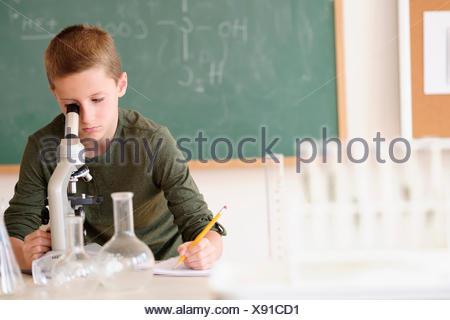 Boy (8-9) looking through microscope - Stock Photo