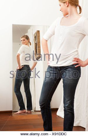 Woman checking her body in the mirror. - Stock Photo