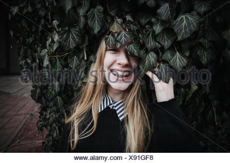 Smiling woman wearing dental braces hiding behind an ivy bush - Stock Photo