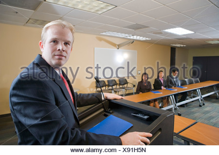 Businessman giving speech in front of Asian business people in boardroom - Stock Photo