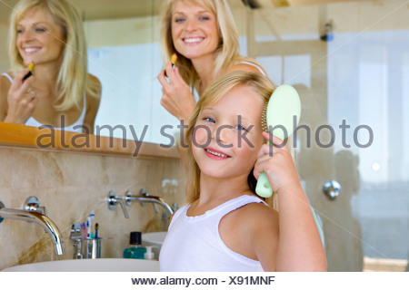 Mother and daughter  in bathroom, girl brushing hair, smiling, portrait - Stock Photo