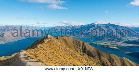 View of mountains and lake, woman jumping at top ridge, Roys Peak, Lake Wanaka, Southern Alps, Otago Region, Southland - Stock Photo