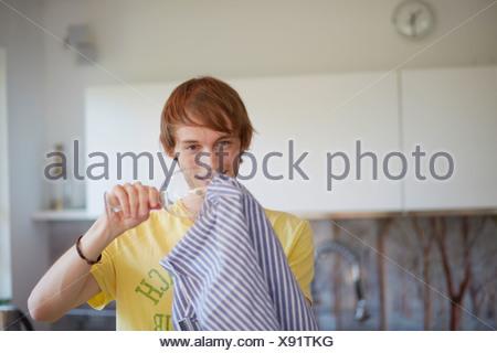Man polishing wine glass in kitchen - Stock Photo