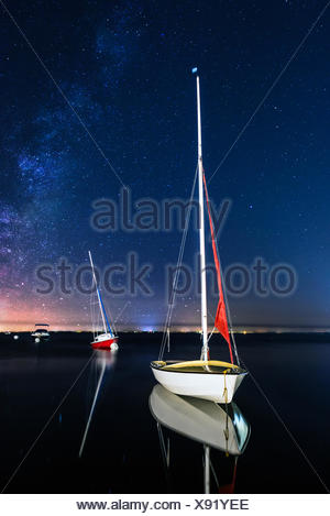Three sailing boats anchored at night - Stock Photo