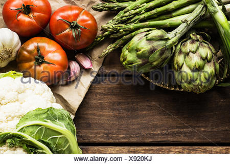 Cauliflower, artichokes, asparagus, garlic and tomatoes on wooden table - Stock Photo