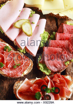 Array of tasty assorted open sandwiches on wholewheat and rye bread topped with gouda cheese, mortadella, roast beef, ham and salami - Stock Photo