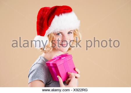 Smiling blond young woman wearing a Santa hat and presenting a gift - Stock Photo