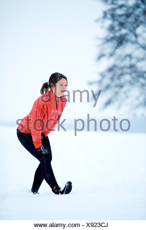 Woman stretching before snow run - Stock Photo