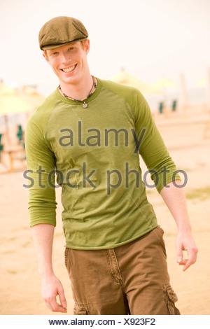 Young man walking on beach - Stock Photo