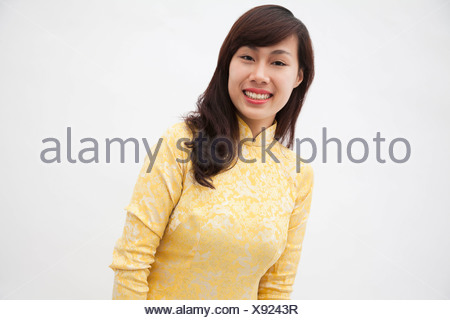 Portrait of smiling young woman wearing a yellow traditional dress from Vietnam, studio shot - Stock Photo