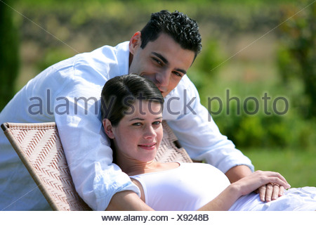 Pregnant woman and boyfriend in the garden - Stock Photo