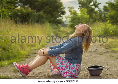 Blonde girl (14-15) sitting on dirt road and laughing - Stock Photo