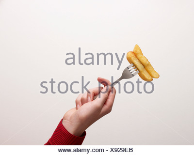Hand holding chips on a fork - Stock Photo