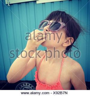 Cute Girl In Swimwear Eating On Beach Against Blue Van - Stock Photo