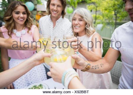 Family toasting lemonade jars at garden party - Stock Photo