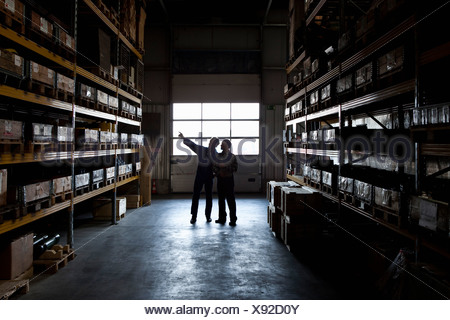 Two manual workers in a metal parts warehouse - Stock Photo