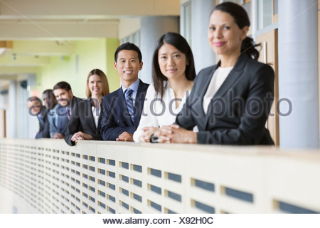 Portrait of confident business team standing by railing - Stock Photo