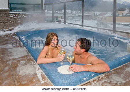 A young couple enjoy conversation and a glass of wine while hottubbing in Jasper, Alberta Canada - Stock Photo