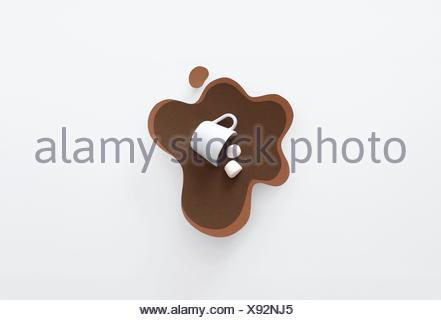 Conceptual mug knocked over, lying in a pool of paper made hot chocolate with marshmallows - Stock Photo