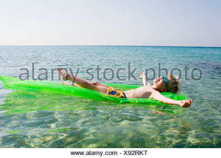 Young boy on an inflatable raft in the water smiling. - Stock Photo