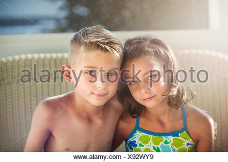 Portrait of boy and girl arms around each other looking at camera smiling - Stock Photo
