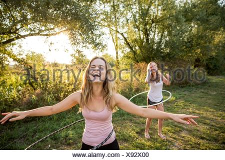 Two young girls in rural environment, fooling around, using hula hoops, - Stock Photo