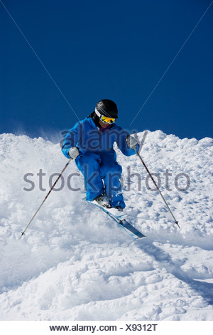 Man in blue skiing down hill. - Stock Photo