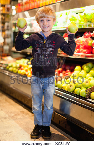 Boy holding fruit at grocery store - Stock Photo