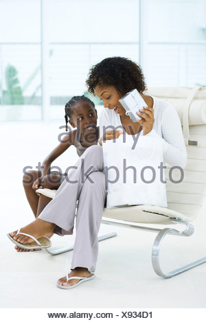 Mother sitting next to daughter, holding up gift, both smiling - Stock Photo