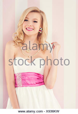 Beautiful girl posing in front of a pink backdrop - Stock Photo