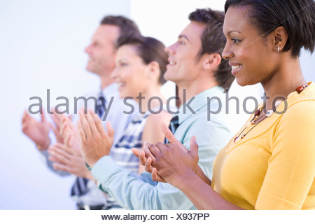 Businessmen and women in row clapping and smiling, close-up, side view - Stock Photo
