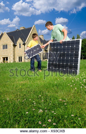 Man and boy holding solar panels in yard - Stock Photo