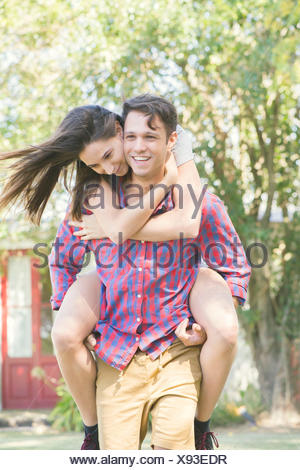 Couple together outdoors, man giving woman a piggyback ride - Stock Photo