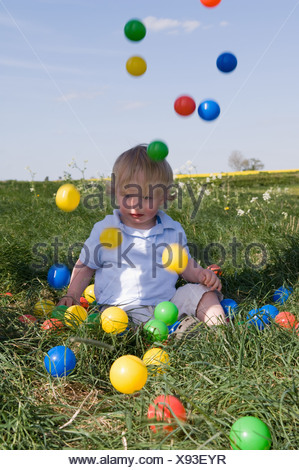 Toddler playing with colored balls - Stock Photo