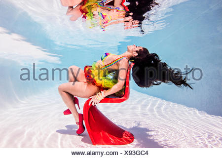 Woman underwater in swimming pool sitting on red plastic chair - Stock Photo