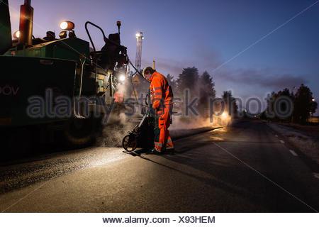 Sweden, Narke, Three manual workers repairing road - Stock Photo