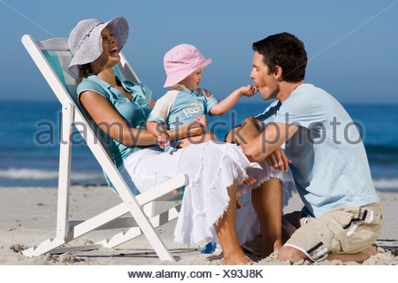 Family relaxing on beach girl 2 3 sitting in mother s lap feeding father laughing side view - Stock Photo