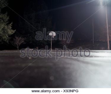 Empty basketball court at night - Stock Photo