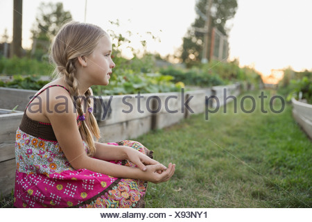 Little girl sitting in community garden - Stock Photo