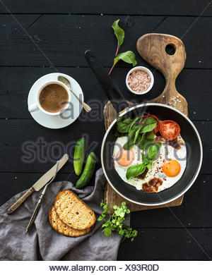Breakfast set. Pan of fried eggs, bacon, tomatoes with bread, mangold and cucumbers, coffee on rustic wooden serving board over - Stock Photo